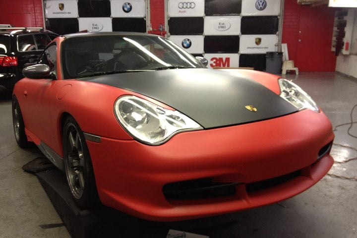 red car with black vinyl wrapped hood